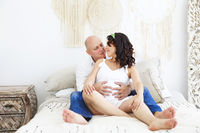 Man and pregnant woman on bed