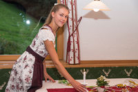 young and attractive waitress sets the table - festive table setting