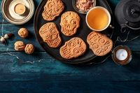 Halloween ginger cookies in the shape of skulls, homemade Dia de los muertos biscuits, overhead shot with a place for text