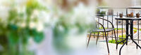 Blurred flower background and view of terraced area with chair and table