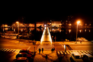 Silhouttes of people on the street crossing the bridge along the port of Zadar at night, Croatia
