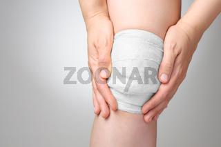 Injured painful knee with white gauze bandage