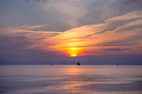 Ships in the open sea at sunset