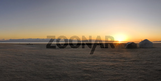 Scenic panorama of sunset on green grasslands in Kyrgyzstan with traditional namodic yurt
