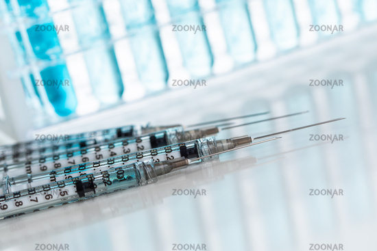 Abstract of Scientific Needle Syringes and Test Tubes Containing Blue Chemical In Rack