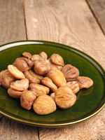 Organic chestnuts on a rustic green plate