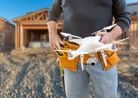 Construction Worker and Drone Pilot With Toolbelt Holding Drone At Construction Site