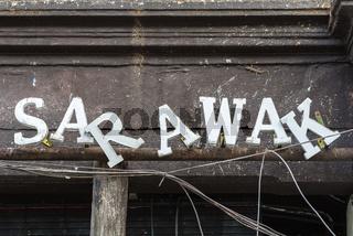 Abgerutschte Buchstaben des Schriftzuges Sarawak an eine Ladenlokal
