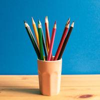 Color pencils in holder on wooden desk with blue background