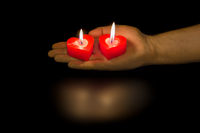 Heart shaped candles in hand