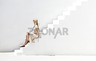 Stylish woman on white stairs in sunlight