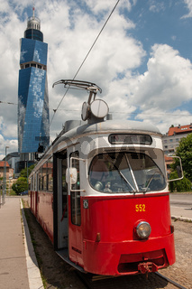 An old tram waits at a tram stop with the Avaz Twist Tower in the background, Sarajevo, Bosnia and H