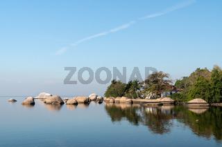 The calm waters of Ilha de Paqueta in Guanabara Bay, Rio de Janeiro, with rocks, trees and buildings