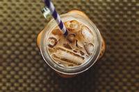 Flatlay of mason jar with iced tea or coffee, selective focus