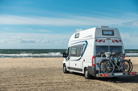 Camping Car RV standing on sand beach at waterfront on sunny day. Romo Bilstrand, Lakolk Strand, Denmark.