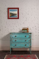 White brick wall with shabby chic vintage turquoise cabinet and hanged painting