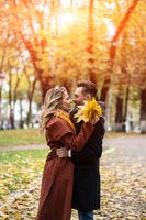 Husband and a wife hugged smile looking at each other in the autumn park. Half-length portrait of a kissing young couple. Outdoor shot of a young couple in love in a autumn park