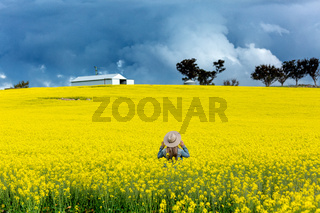 Farm girl in field of canola with storm looming