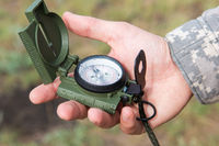 Man with compass in hand outdoor