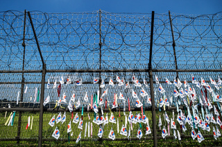 DMZ, Freedom bridge, Republic of Korea - September 8 2017: Fence with barbed wire and south korean flags at the demilitarised zone DMZ at the freedom bridge, South Korea, Asia