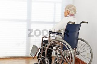 Einsame Seniorin schaut aus Fenster