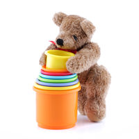 Brown teddy bear playing with toy pots containers