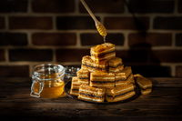 Plate with slices of honey cake and jar