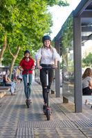 Trendy fashinable teenager girls riding public rental electric scooters in urban city environment. Eco-friendly modern public city transport