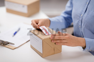 woman sticking fragile mark to parcel box