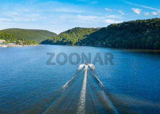 Speedboat on Cheat Lake on a summer evening with boats docked in marina