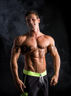 Handsome shirtless bodybuilder smiling at camera on dark