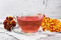 Tea herbal of marigolds in cup on old board