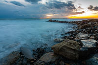 Seascape at sunset, waves roll ashore