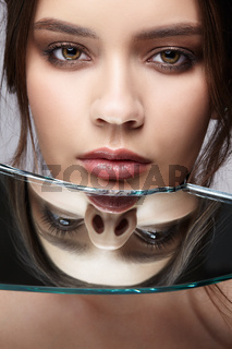 Portrait of a beautiful girl with reflection in a mirror splinter
