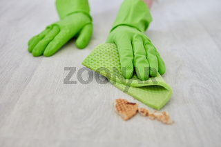 Hände der Putzhilfe wischen Krümel vom Fußboden