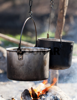 Cooking in two sooty old cauldrons on bonfire with smoke at forest