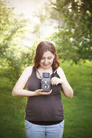 Pregnant woman with photo camera standing in park