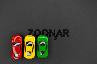 Yellow, green and red toy cars on a gray background, top view.