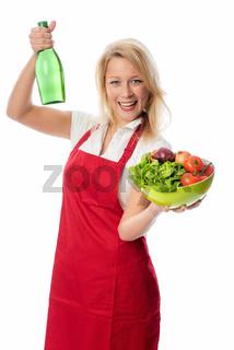 frau hält eine schale salat und eine flasche essig