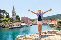 Woman traveler wearing straw summer hat and backpack, standing at edge of the rocky cliff, relaxing, arms up to the sky, enjoying beautiful panoramic view of Veli Losinj, Losinj island, Croatia