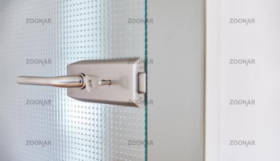 Offene Glastür im Büro mit Türklinke und Schlüssel im Türschloss