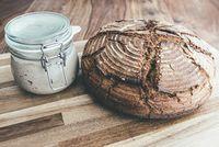 rye sourdough bread and sourdough starter in jar on wooden table