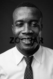 Studio shot of young African businessman against gray background