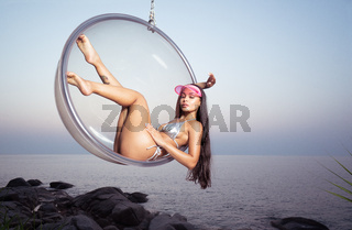 Fashion girl on glass chair outdoors over sky and sea background during sunset