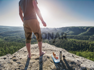Man take brak for snack while climbing in rocks. Hiker in shorts