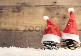 Two pine cones with Santa cap on snow and wooden background