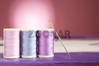 Sewing threads and needle on a painted wooden box