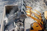 Bulldozer loader uploading concrete debris into dump truck