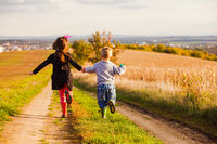 Kids have fun are running on country road