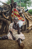 TOPOSA TRIBE, SOUTH SUDAN - MARCH 12, 2020: Woman smoking pipe while sitting on ground near lumber and girl in colorful garment in village of Toposa Tribe in South Sudan, Africa
